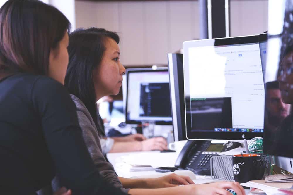 講師からパソコン操作を教わる女性
