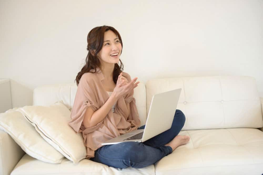 パソコンを前に喜ぶ女性